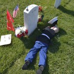Boy in Marine uniform lies next to his father's grave at Arlington National Cemetery